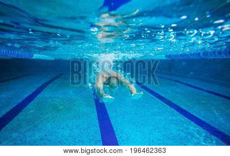 Young man swimming underwater in indoor pool