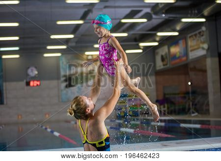Young mother or instructor and preschool girl having fun in indoor swimming pool