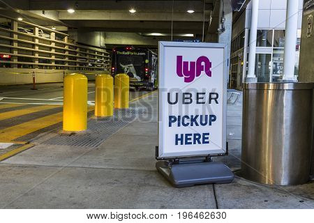 Indianapolis - Circa July 2017: Ride sharing companies Lyft and Uber pickup spot at the airport. Lyft and Uber have replaced many Taxi cabs for transportation I