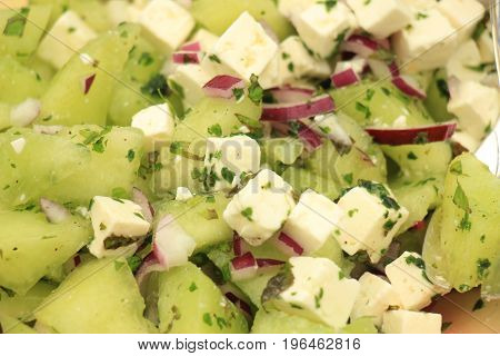 Green melon salad with soft white feta cheese and herbs