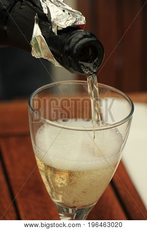 Man pouring white wine at a dinner table
