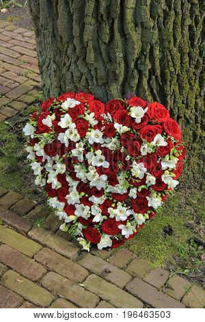 Red and white heart shaped sympathy flowers or funeral flowers near a tree