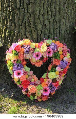 Heartshaped pastel sympathy flowers or funeral flowers near a tree