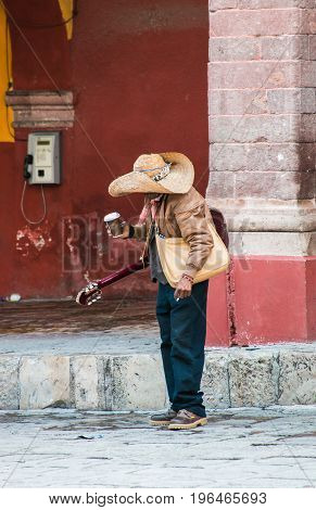 Old man with guitar and coffee cup in the Jardin (garden) of San Miguel de Allende, MX.