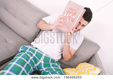 Young Man Eating Popcorn And Watching Movies