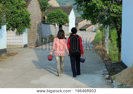 A Chinese mother and daughter walk hand-in-hand along the road carrying their baskets of cherries in the China countryside.