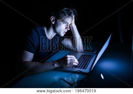 Feeling Exhausted Frustrated Young Man While Sitting In Front Of Laptop In The Night