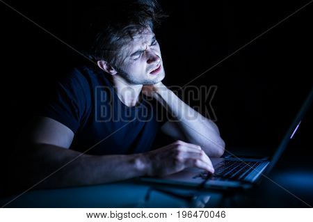 Feeling Exhausted Frustrated Young Man With Neck Pain While Sitting In Front Of Laptop In The Night