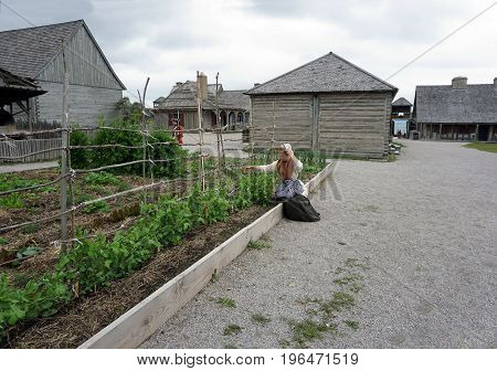 MACKINAW CITY, MICHIGAN / UNITED STATES - JUNE 18, 2017: A costumed interpreter sits beside an elevated vegetable garden in Fort Michilimackinac, in the Colonial Michilimackinac State Park.