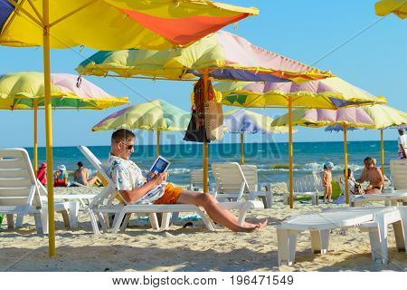 LAZURNE, KHERSON REGION, UKRAINE: July 05: A man reading a book on a beach on a chaise lounge.