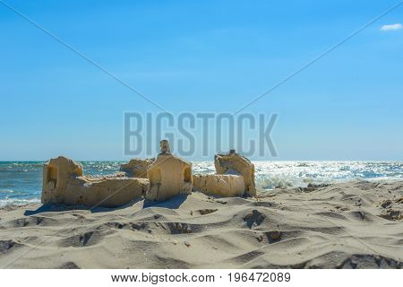 The sand castle on the seafront on the background of the light path of the sun
