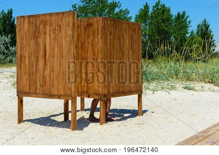Locker room with wooden boards on the beach on the sand