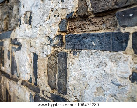 Highly textured solid wall built from tiles and bricks, held together by cement and plaster. Shallow depth-of-field closeup image.