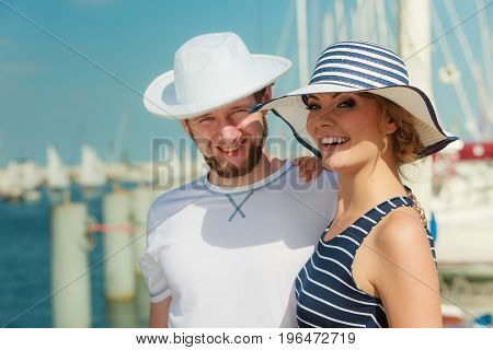 Travel tourism and people concept. Young tourist couple on vacation standing in front of boats in marina