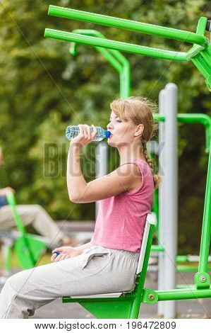 Woman with drinking water relaxing at outdoor gym. Young girl taking break from fitness exercise. Healthy lifestyle.