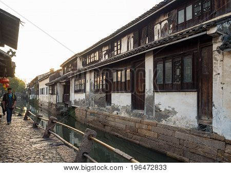 Suzhou, China - Nov 5, 2016: People walking along a peaceful narrow path of cobblestone at the historic Zhouzhuang Water Town. Path is along a water canal channel.