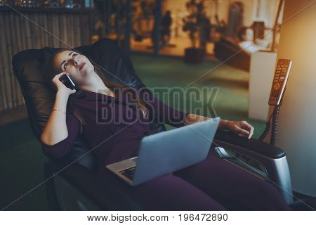 Beautiful caucasian businesswoman is chilling on modern leather massage chair laying relaxed with laptop on her knees and having conversation with her family during lunch time in office chillout