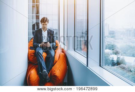 Handsome businessman is secluded and sitting on orange pillow between white column and window of skyscraper while having online chat via his smartphone rainy cityscape in background
