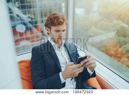 Handsome adult bearded businessman in formal suit is having rest between work meetings and sitting on orange sofa or pillow near office window of high skyscraper floor during rain outside
