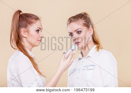 Technology communication and friendship concept. Two teen girls casual style using mobile phone reading message funny surprised emotion on face