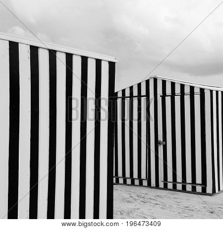 Vertical Striped beach shed on sand at Miami USA in monochrome.