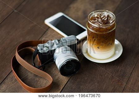 Iced coffee and the camera on a wooden table