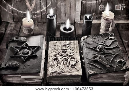 Witch magic book with black and wax burning candles in the darkness. Mystic still life with scary occult objects, horror Halloween and black magick concept, fortune telling or divination