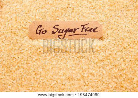 Go Sugar Free - Handwritten On Label Sitting In Raw Sugar Granules