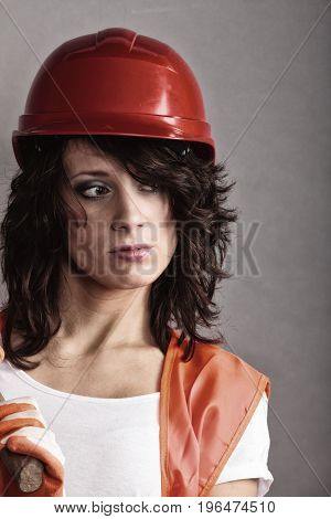 Sex equality and feminism. Sexy girl in safety helmet and orange vest. Attractive woman working as construction worker.