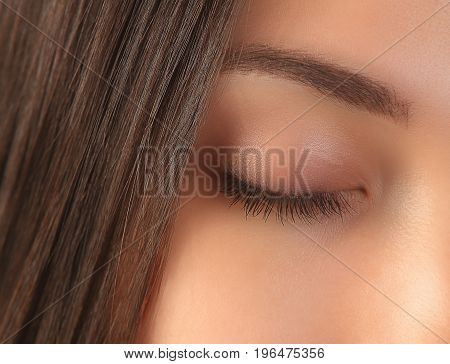 Closed girl eye close-up. Woman face with clean perfect skin. Brunette girl face with smooth skin closeup.