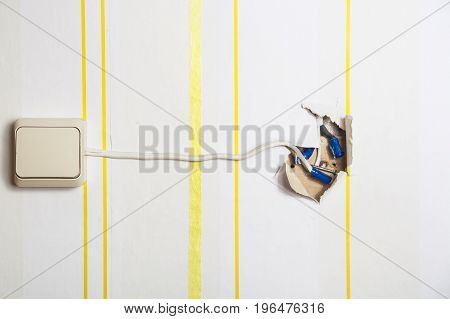White light switch with a protruding wire on a white wall in yellow stripes