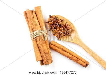 Close up brown cinnamon stick with star anise spice in wooden spoon isolated on white background