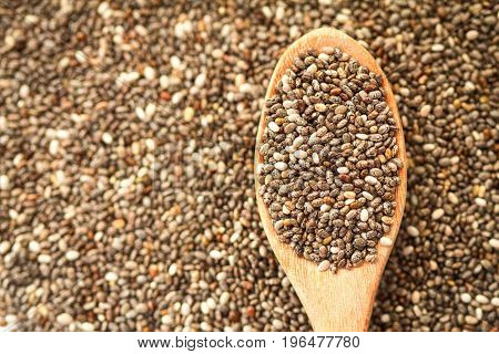 Close up chia seeds in wooden spoon on chia seeds background