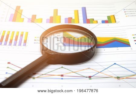 Magnifier on white paper, black magnifier on paper with numbers and charts.