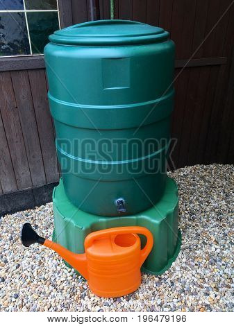 Big green water butt for rainwater with watering can in the garden