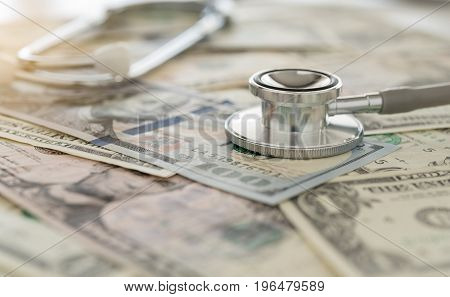 medical cost stethoscope on dollar banknote money. concept of health care costs finance health insurance funds.
