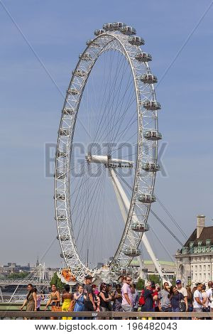 LONDON UNITED KINGDOM - JUNE 21 2017: View on London Eye and tourists on Westminster Bridge. It was erected in 1999 is the most popular paid tourist attraction in the UK with over 3.75 million visitors annually