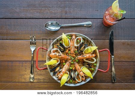Paella With Seafood Vegetables And Saffron Served In The Traditional Pan Top View.