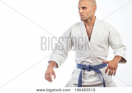 A young bald man in a white kimono and blue belt for a kimono sambo jiujitsu stands in a fighting pose on an isolated white background