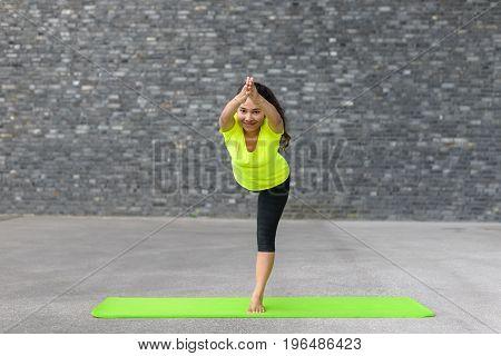 Young Woman Practising Vrksasana Yoga Pose