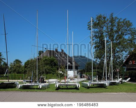 White Catamarans Sailboats Ashore on Grass Field in Summer