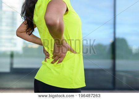 Woman Wearing Sportswear Holding Painful Back
