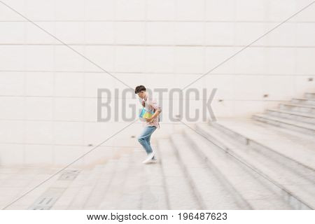Male student going down the stairs blurred motion