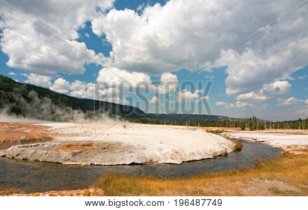 Iron Spring Creek and Cliff Geyser under cumulus cloudscape in Black Sand Geyser Basin in Yellowstone National Park in Wyoming United States