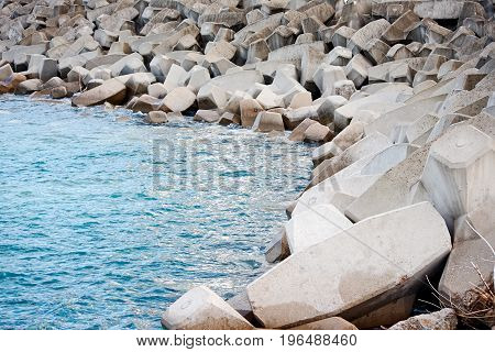 Breakwater with concrete blocks for protection of coast sunset