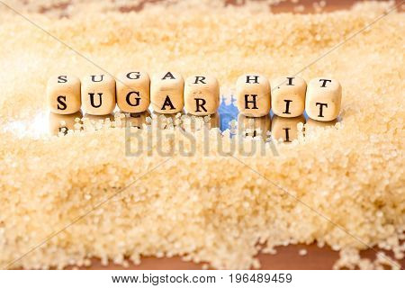 Sugar Hit - In Wooden Block Letters In Granules Of Sugar Reflected In Mirror Background