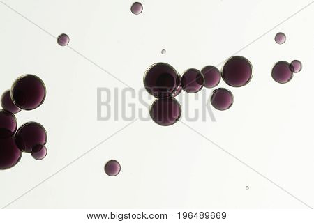 Dark red air bubbles over a light background.
