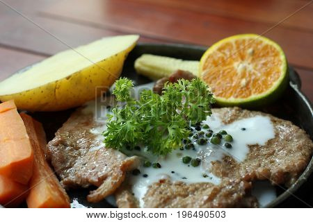 Grilled steaks with baked potatoes and green vegetables on top.