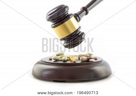 Law gavel and drugs tablets and pills on the wooden sound block isolated on a white background justice and medicine concept