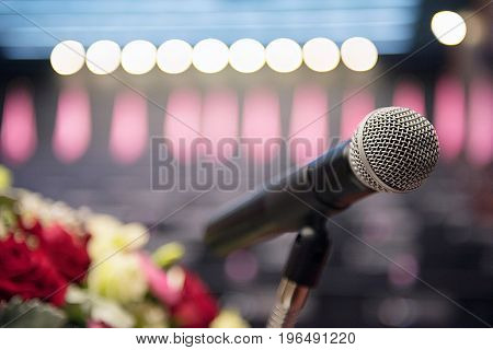 Microphone over the blurred business conference hall or seminar room Blurred background.